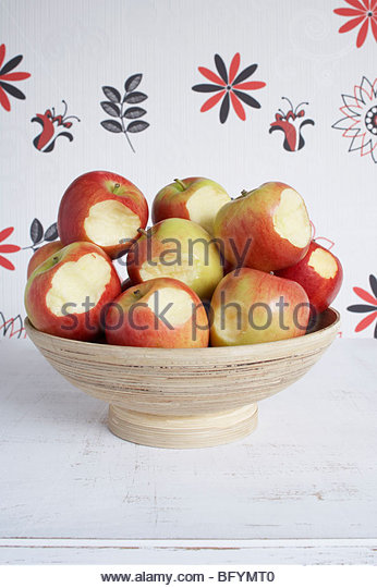 bowl full of bitten apples - Stock Image