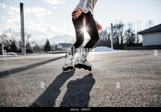 Low section of young man inline skating - Stock Image