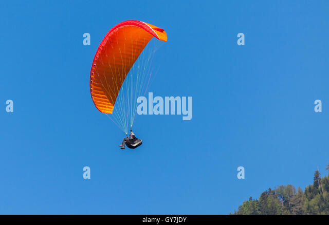 Paraglider with red glider in front of blue sky - Stock Image