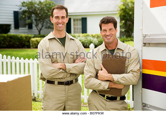 Removal men standing beside their van with packing boxes - Stock Image