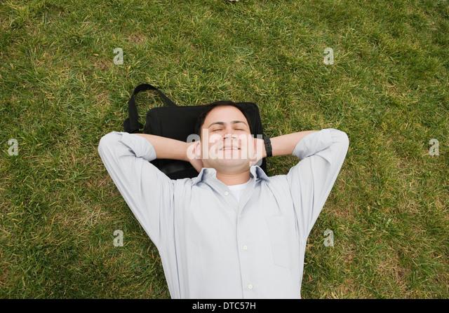 Businessman lying on grass - Stock-Bilder