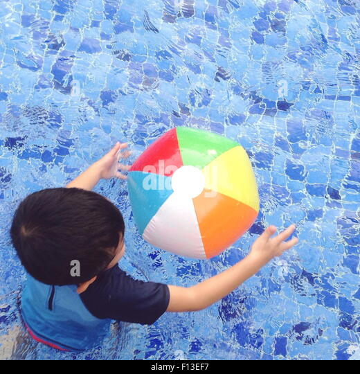 Overhead view of a boy playing with a beach ball in the swimming pool - Stock Image