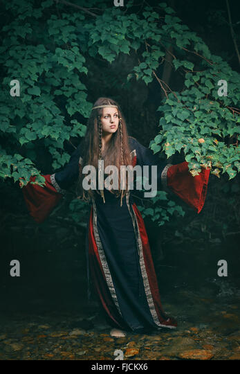 Beautiful young woman with medieval dress in a forest stream - Stock-Bilder