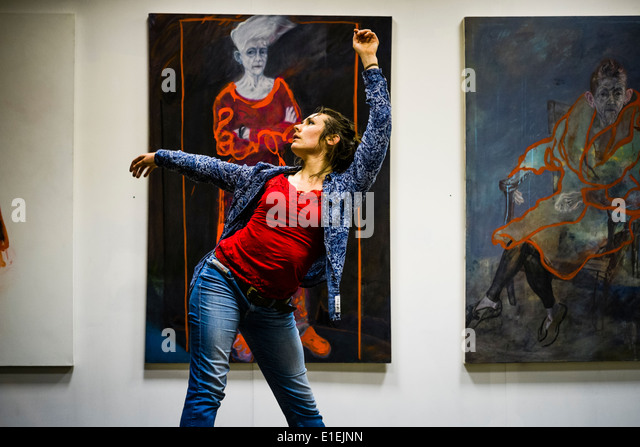A woman dancer performing in a creative response to paintings by Annie Morgan Suganami in an art gallery, UK - Stock-Bilder