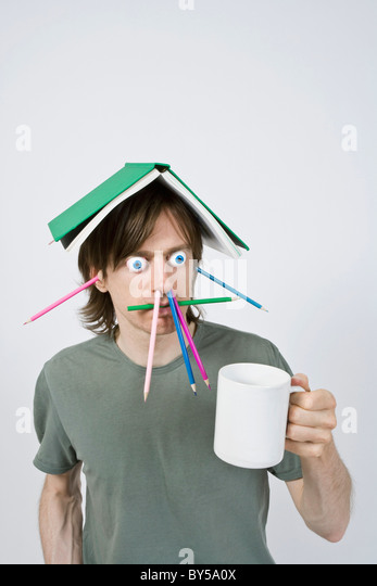 Bizarre man with pencils, book and coffee - Stock Image