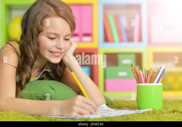 Little girl painting with pencil in her room  - Stock Image