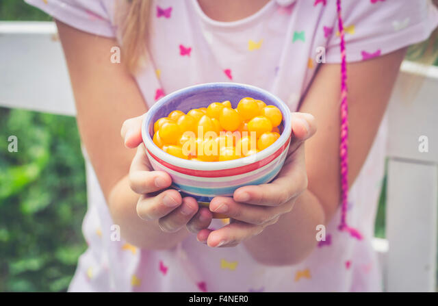 Girl holding bowl with tomberries, yellow mini tomatoes - Stock Image