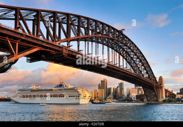 Oversized ocean cruise liner passing by under the Sydney Harbour Bridge at sunset backgrounded by city skyscrapers - Stock Image
