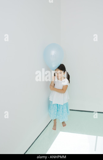Girl standing in corner holding balloon, looking up at camera - Stock Image