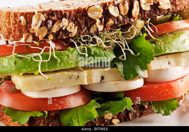 Vegetarian health bread sandwich with avocado, cheese, mushrooms, lettuce, sprouts and tomatoes - Stock Image