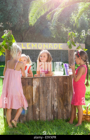 Four girls buying and selling at lemonade stand in park - Stock Image