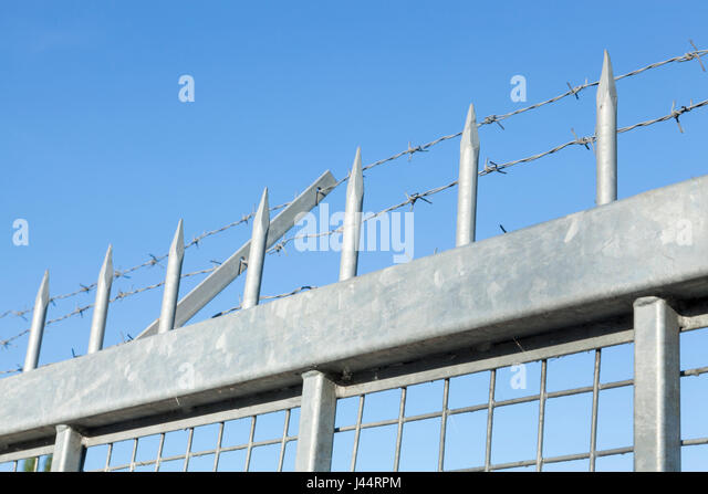 Security fencing with spikes and barbed wire - Stock Image