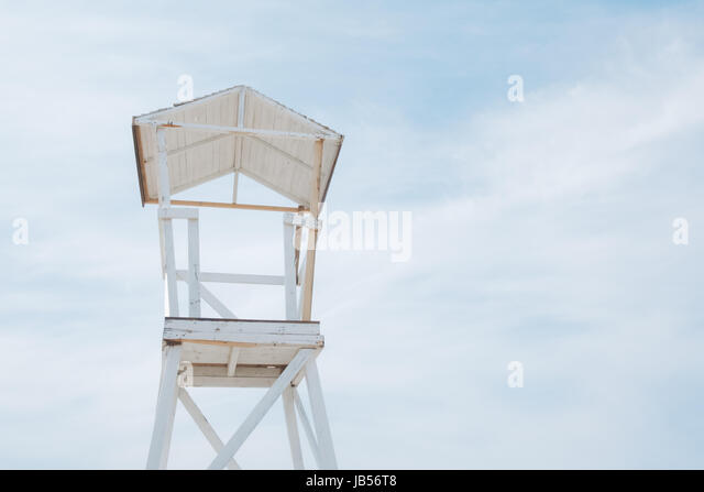 Wooden beach stand on blue sky background ashore of the Mediterranean sea. Sunny day with blue sky and fluffy clouds. - Stock Image