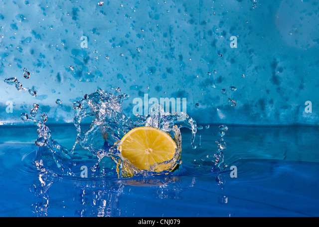 Lemon splashing into water - Stock Image