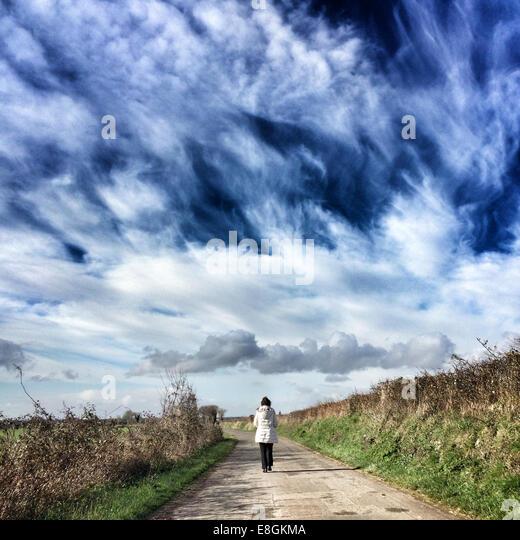 Woman walking down path - Stock-Bilder