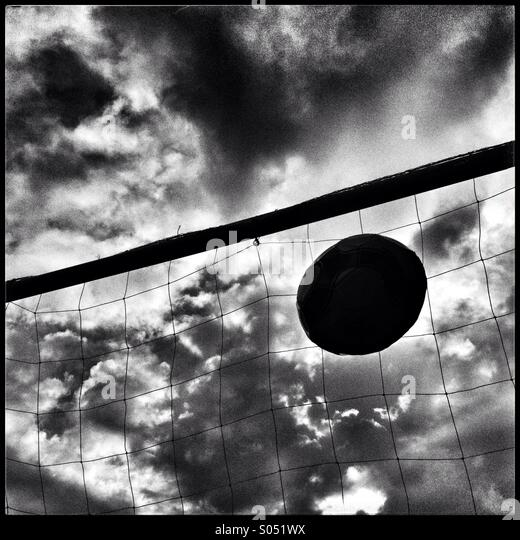 Football flying into net against dramatic sky - Stock Image