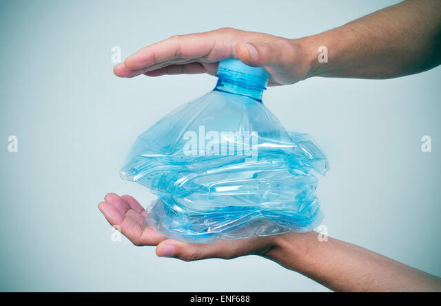 closeup of a young caucasian man smashing a plastic bottle with his hands - Stock Image