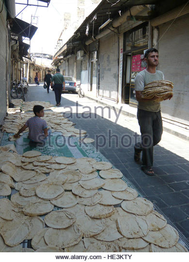 A baker displays traditional bread during the first day of Ramadan in the Old city of Aleppo, Syria, August 11, - Stock Image