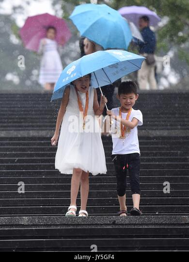 Beijing, China. 18th Aug, 2017. Tourists walk off stairs in rain at the National Centre for the Performing Arts - Stock Image