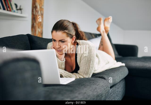 Portrait of beautiful young woman working on laptop while lying on sofa. Female using laptop at home. - Stock-Bilder
