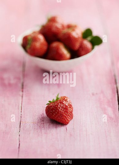 Strawberries in bowl on table, close up - Stock Image