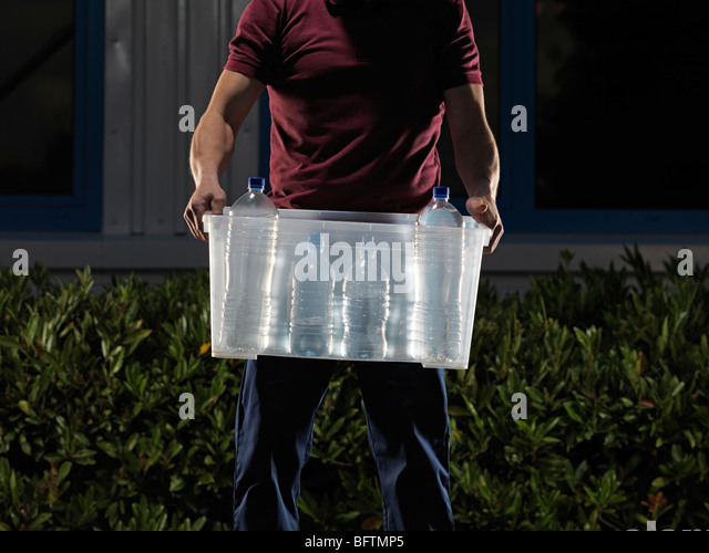 man carrying box of water at night - Stock Image