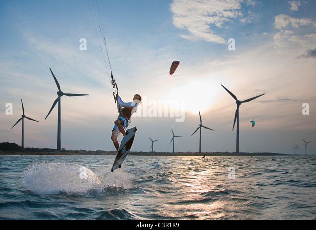 Croatia, Zadar, Kitesurfer jumping in front of wind turbine - Stock Image