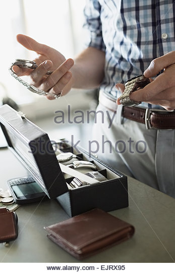Close up of man selecting wristwatch from box - Stock Image