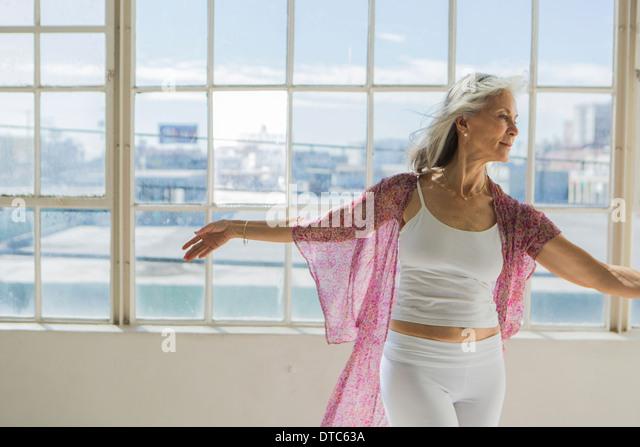 Graceful senior woman dancing in sunlit apartment - Stock Image