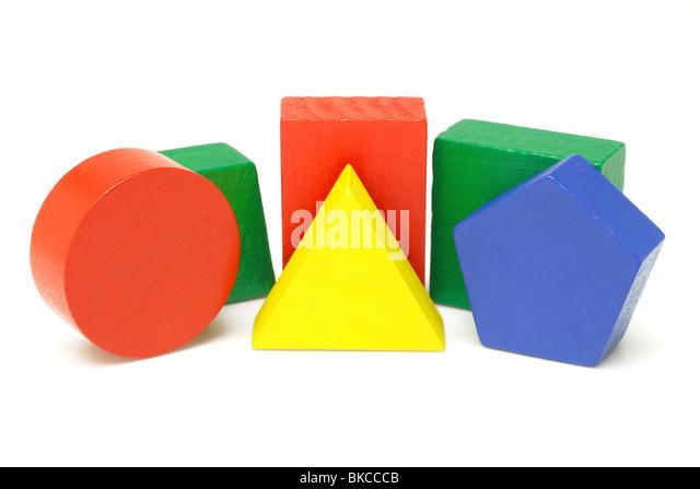 Colorful wooden geometric blocks on white background - Stock Image