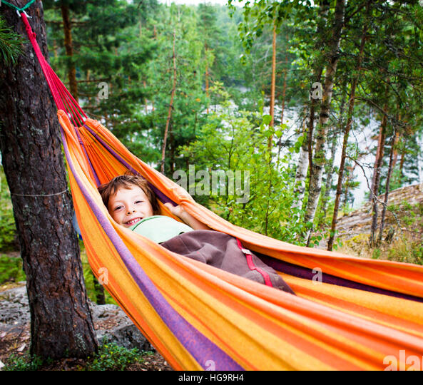 little cute real boy in hammock smiling against landscape with forest and lake hight on mountain, lifestyle people - Stock Image