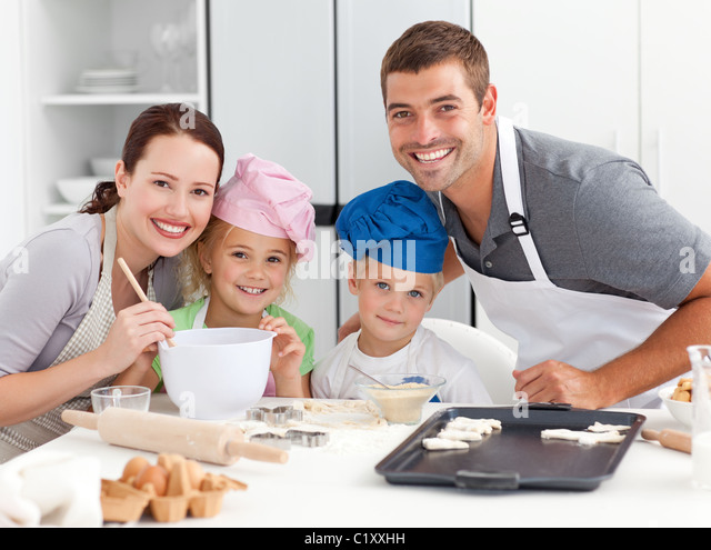 Portrait of a joyful family cooking littles cakes - Stock Image