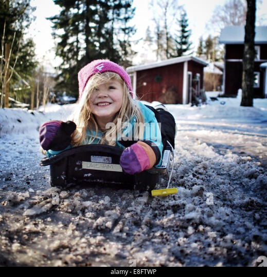 Sweden, Girl (6-7 years) lying on sledge - Stock Image