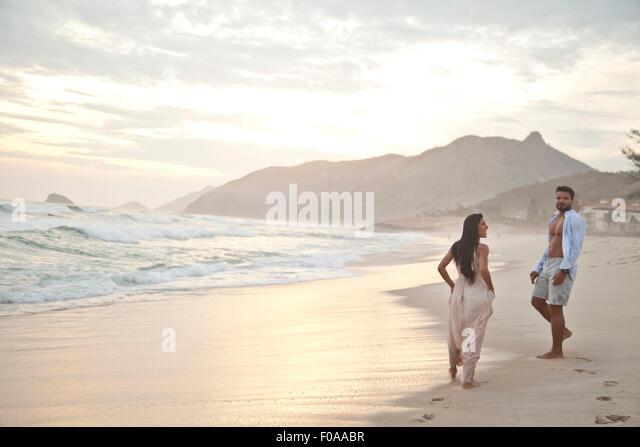Mid adult couple on beach, Rio de Janeiro, Brazil - Stock Image