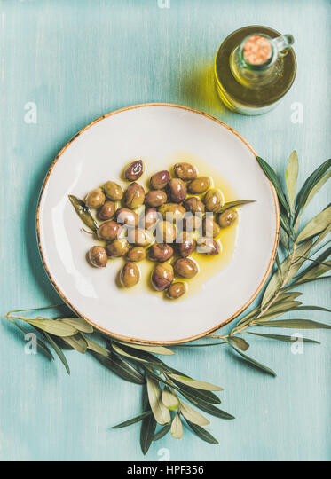 Pickled green Mediterranean olives on white ceramic plate, olive tree branch and virgin olive oil in glass bottle - Stock Image