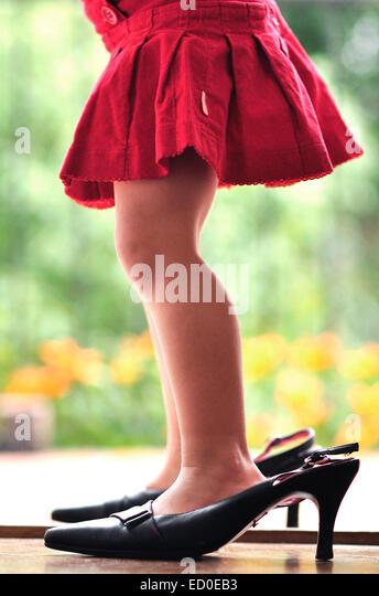 Legs of girl (2-3) in high heels - Stock Image