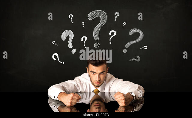 Sitting businessman under question marks - Stock Image