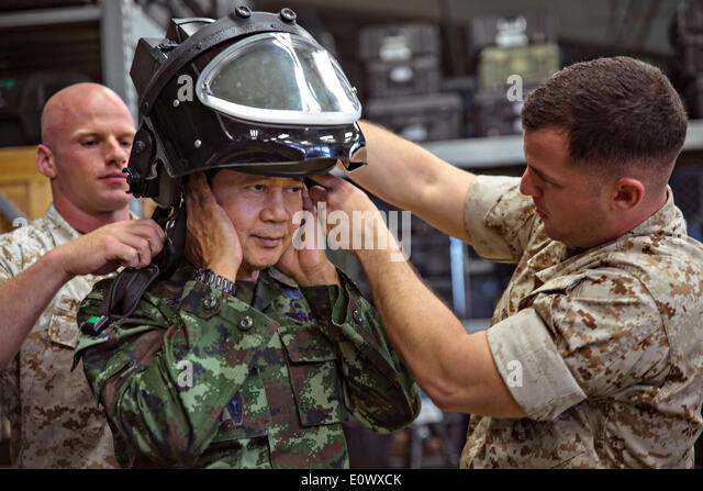 Two US Marines help Royal Thai Armed Forces Lt. Gen. Krisda Norapoompipat put on the helmet from an advanced bomb - Stock Image