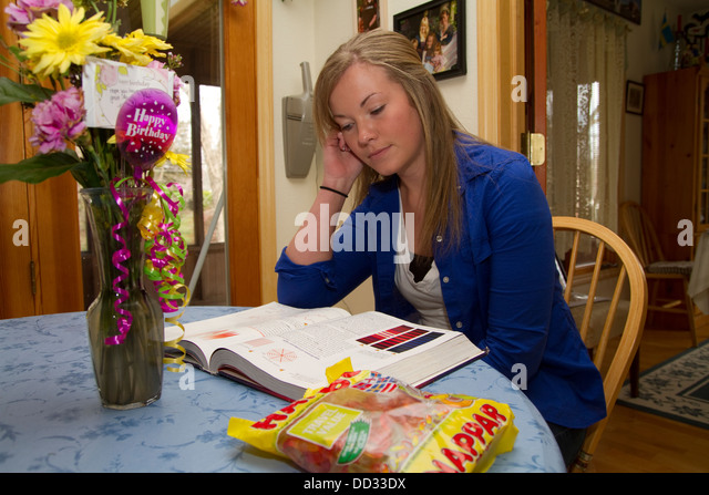 Young female student at kitchen table doing homework. Lindsborg, Kansas. - Stock Image
