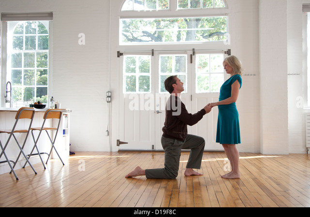 Couple in dance studio, man on one knee - Stock Image