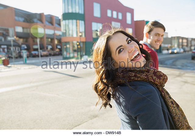 Cheerful woman looking back on city street - Stock-Bilder