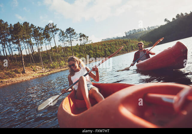 Happy young couple canoeing on lake together. Man and woman kayaking on a summer day. - Stock Image