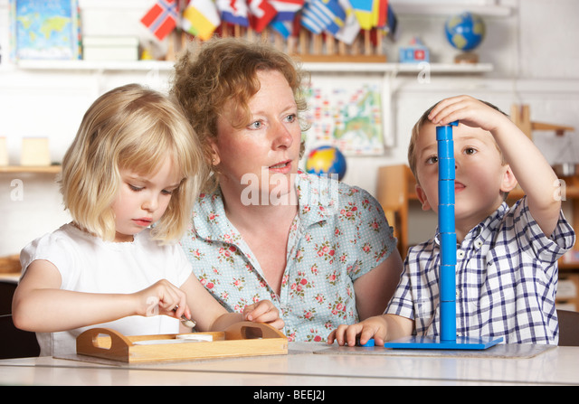 Adult Helping Two Young Children at Montessori/Pre-School - Stock Image