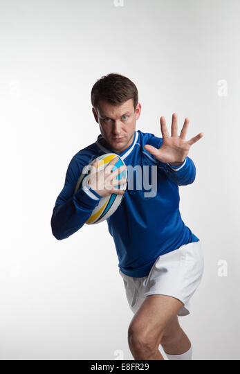 Rugby player running with rugby ball - Stock Image