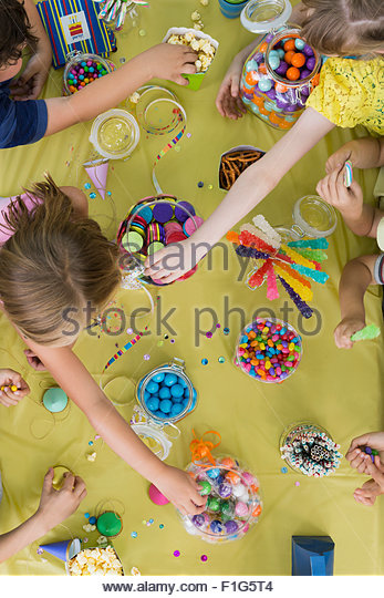 Overhead view kids reaching candy table birthday party - Stock Image