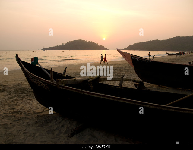 Fishing boats on Palolem beach in Goa in South India at sunset - Stock Image