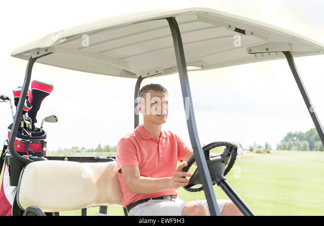 Middle-aged man driving cart at golf course - Stock Image