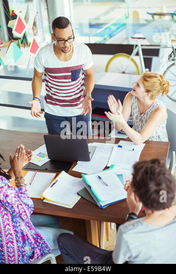 People applauding colleague in office - Stock Image