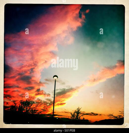 Lone street lamp against a vibrant sunset sky. - Stock Image