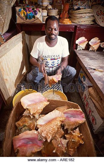 Bahamas New Providence Nassau Straw Market man makes conch shells into souvenir horns - Stock Image